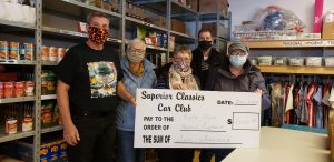 Superior Classic Car presents a cheque to the Harvest Food Cupboard.